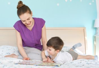 Portrait of cheerful lovely young mother reads fairy tales for her son, sit together at bed against cozy bedroom interior. Curious small male kid looks attentively at book views pictures with interest